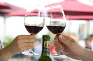 Two people toast with red wine at dinner